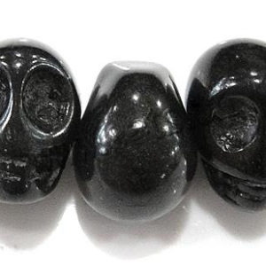 En rad blänkande svarta stenpärlor i form av döskallar
