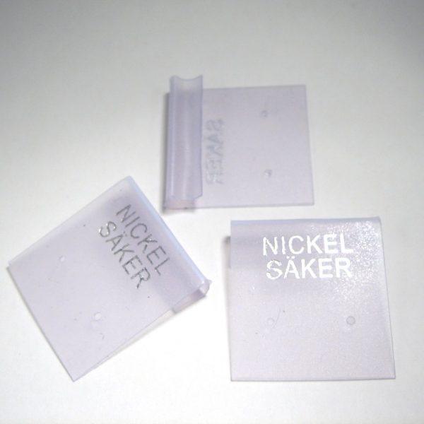 Plastkarta för örhängen. 25x25mm. Text: NICKEL SÄKER. Frostad.